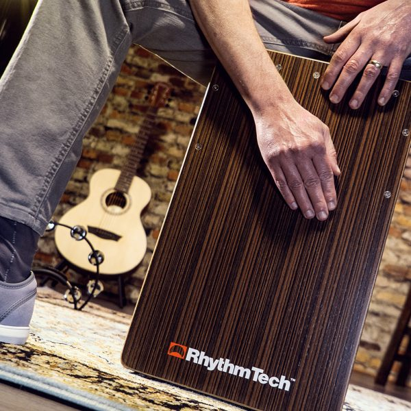 partial view of man playing Rhythm Tech cajon in front of acoustic guitar and brick wall