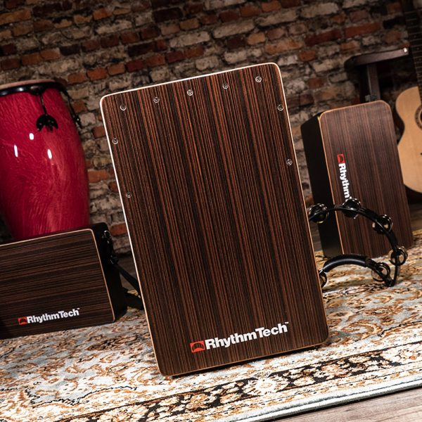 Rhythm Tech cajon in front of two other cajons, a djembe, an acoustic guitar, and a brick wall