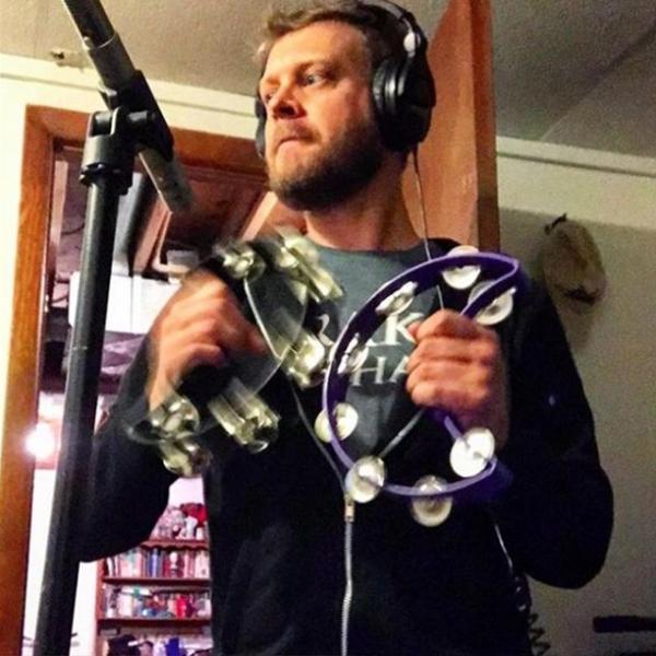 man wearing headphones using two crescent-shaped tambourines