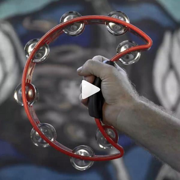 man's hand holding red crescent-shaped tambourine
