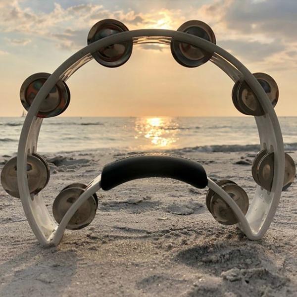 white crescent-shaped tambourine at beach during sunset