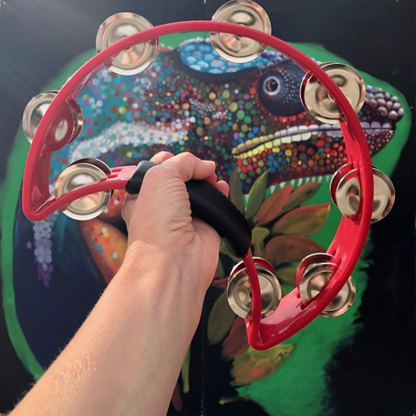 red crescent-shaped tambourine held in front of street art