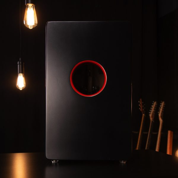 back view of Rhytm Tech cajon with two hanging lights and electric guitars in background