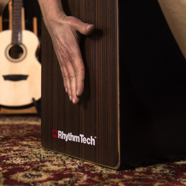 closeup of hand playing Rhythm Tech cajon in front of acoustic guitar