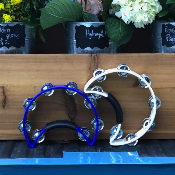 blue and white Rhythm Tech crescent-shaped tambourines in front of potted flowers in wooden box