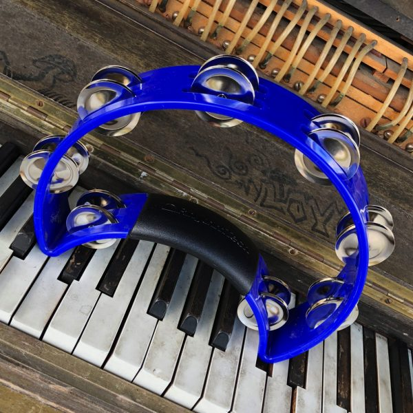 blue Rhythm Tech crescent-shaped tambourine on vintage piano