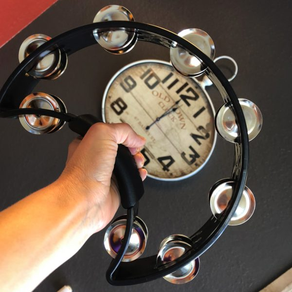 hand holding black Rhythm Tech crescent-shaped tambourine in front of clock hanging on wall