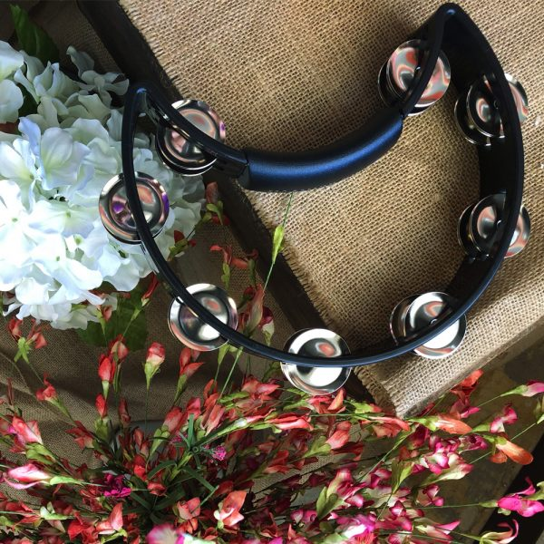 black Rhythm Tech crescent-shaped tambourine on piece of burlap material beside white and pink flowers
